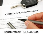 Document and Form of a Vehicle Sales Agreement with Hand signing pen and car key - stock photo