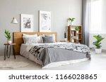 patterned blanket on wooden bed ... | Shutterstock . vector #1166028865