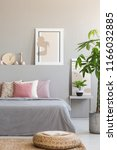 pouf and plant next to grey bed ... | Shutterstock . vector #1166032885