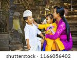 happy balinese mother playing... | Shutterstock . vector #1166056402