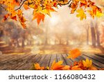 wooden table with orange leaves ... | Shutterstock . vector #1166080432