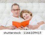 happy elderly couple reading a... | Shutterstock . vector #1166109415