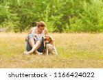 Stock photo animal lover woman animal lover sitting on grass with her pets 1166424022