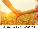 hands of mother and daughter on ... | Shutterstock . vector #1166548285