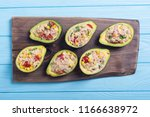 avocado stuffed with salad from ... | Shutterstock . vector #1166638972