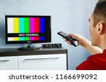 remote control in hand in front ... | Shutterstock . vector #1166699092