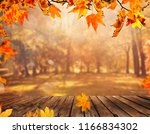 wooden table with orange leaves ... | Shutterstock . vector #1166834302