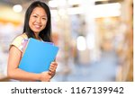 young woman holding books | Shutterstock . vector #1167139942