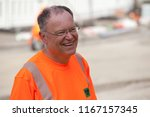 Small photo of Elsfleth, Germany - August 29, 2018: Stephan Weil, Prime Minister of Lower Saxony in orange Shirt with reflecting safety stripes while practical studies at a construction site for roadworks