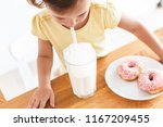 little girl eating donuts and... | Shutterstock . vector #1167209455