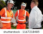 Small photo of Elsfleth, Germany - August 29, 2018: Stephan Weil, Prime Minister of Lower Saxony in orange safety working suit and helmet tagether with an other worker talks to a man in white shirt
