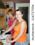 Two women makes pie with fillings in  kitchen - stock photo