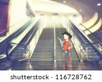 a small boy next to stairs and an escalator at an airport - stock photo