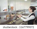 chef handing food dish to... | Shutterstock . vector #1167799072