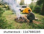 man build fire in forest  car... | Shutterstock . vector #1167880285