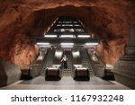 Small photo of STOCKHOLM, SWEDEN - AUGUST 24, 2018: Person rides escalator in Stockholm metro (T-bana) underground station in Sweden. Stockholm metro is known for its artistic station interiors.