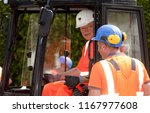 Small photo of Elsfleth, Germany - August 29, 2018: Stephan Weil, Prime Minister of Lower Saxony, sits in orange working dress and white helmet in an excavator in a construction zone and talks to a worker