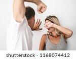 man beating helpless woman at... | Shutterstock . vector #1168074412