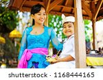 happy balinese mother in temple ... | Shutterstock . vector #1168444165