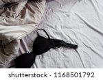 black bra on rumpled grey bed | Shutterstock . vector #1168501792