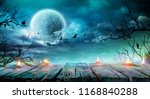 Stock photo halloween background old table with candles and branches at spooky night with full moon 1168840288