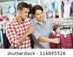 Young man and woman family choosing outerwear during clothing shopping at supermarket store - stock photo