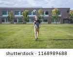 happy teenager tossing a soccer ... | Shutterstock . vector #1168989688