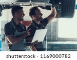 mechanics checking wheel... | Shutterstock . vector #1169000782