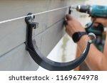 man hands installing dark grey... | Shutterstock . vector #1169674978