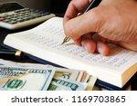 bookkeeper writing financial... | Shutterstock . vector #1169703865