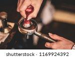 barista presses ground coffee... | Shutterstock . vector #1169924392