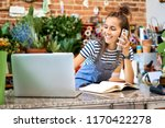 young florist looking at laptop ...   Shutterstock . vector #1170422278