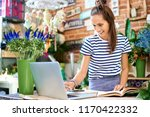 cheerful florist looking at... | Shutterstock . vector #1170422332