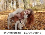 Stock photo young beautiful girl playing with a dog in the park autumn sunny day 1170464848