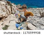 little boy cleaning up beach... | Shutterstock . vector #1170599938