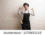 Small photo of Young baker indian woman against a bricks wall proud and confident, pointing fingers, example to follow, concept of satisfaction, arrogance and health