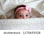 Stock photo cute baby girl with a bow on her hair laying on her bed with a teddy bear 1170655528