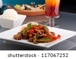 A fresh dish of Thai style roast chile basil duck with mixed vegetables white jasmine sticky rice and Thai iced tea. - stock photo