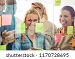 Diverse group of businesspeople laughing while standing in an office brainstorming together with sticky notes on a glass wall