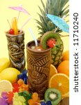Tropical drinks served on tiki mugs and fruits display - stock photo