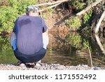 a fisherman sits near a river...   Shutterstock . vector #1171552492