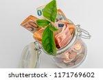coins and bills in a glass jar... | Shutterstock . vector #1171769602