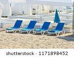 row of blue empty sunbeds on... | Shutterstock . vector #1171898452