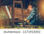 Small Housework Project. Caucasian Men in His 30s with Gasoline Chainsaw Preparing For Some Work Inside the Barn. - stock photo