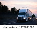 Small photo of Big rigs semi trucks carry goods on the roads without interruption, regardless of the time of day from early morning until late at night, truckers are rushing along the roads timely delivering goods
