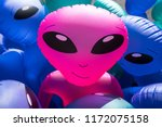 Small photo of Colorful alien blowup dolls with large black eyes on sale in a carnival stand.