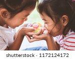 two asian child girls holding... | Shutterstock . vector #1172124172