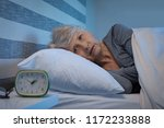 worried senior woman in bed at... | Shutterstock . vector #1172233888