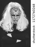 Small photo of Man with reptilian skin and long grey hair standing in dark clothes with hands folded on black background. Horror and fantasy concept