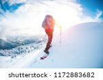 Small photo of A man in snowshoes in the mountains in the winter. A climber with trekking sticks walks through the snow. Winter ascent. Beautiful sky with clouds.